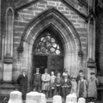 Group of men standing outside St Peter's Church, Belper with a set of new bells