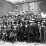Photograph of group of men standing by charabanc