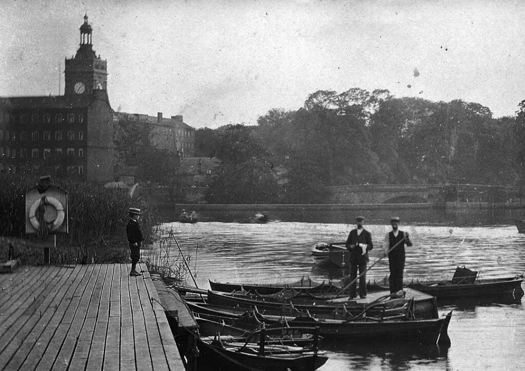 Boatmaster with boats at Belper River Gardens with the West Mill in the background.