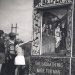 Some children looking and pointing at a well dressing on The Fleet, Belper